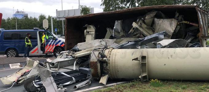 Container met oud ijzer valt van vrachtwagen